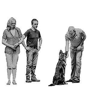 Arnoud Busscher aan het lesgeven in het bos met een herderpup en een man en een vrouw